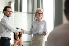 Happy female boss shaking hand congratulating male worker with promotion royalty free stock images