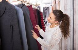 Happy female brunette choosing trousers in shop Stock Photo