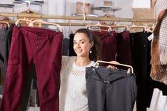 Happy female brunette choosing trousers Stock Photos