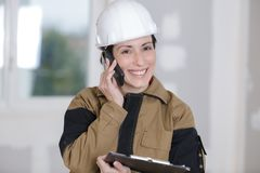 Happy female builder talking on phone Stock Photos