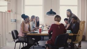 Happy female business coach gives guides to employees. Multiethnic teamwork by the table at office board meeting 4K. stock footage