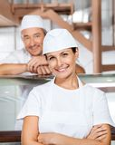 Happy Female Butcher With Colleague At Butchery. Portrait of happy mature female butcher with male colleague in background at butchery stock photos