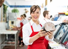 Happy Female Butcher Holding Large Ham Royalty Free Stock Images
