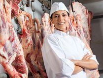 Happy Female Butcher In Slaughterhouse. Portrait of happy mid adult female butcher standing arms crossed in slaughterhouse stock image