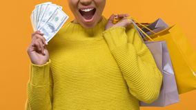Happy female buyer with shopping bags holding dollar bills, purchase cash back. Stock footage stock video footage