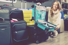 Happy female buying travel suitcase in store. Happy female buying travel suitcase in haberdashery store Stock Photo