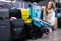 Happy female buying travel suitcase in store Royalty Free Stock Photography