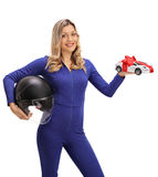 Happy female car racer holding helmet and model car Royalty Free Stock Image