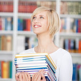 Happy female carrying books in library Royalty Free Stock Photography