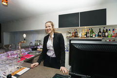 Happy female cashier at counter in restaurant Stock Images
