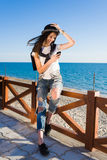 Happy female chatting on mobile phone while enjoying sunny afternoon on the beach Royalty Free Stock Images