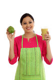 Happy female chef holding glass of avocado smoothie Stock Photo