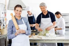 Happy Female Chef Holding Rolling Pin While Stock Images