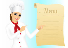 Happy female chef pointing at menu Stock Images