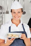 Happy Female Chef Presenting Cookies Royalty Free Stock Image