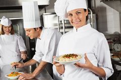 Happy Female Chef Presenting Pasta In Kitchen Stock Photos