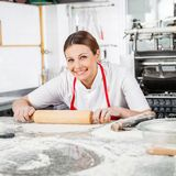 Happy Female Chef Rolling Pasta Sheet At Counter Stock Image