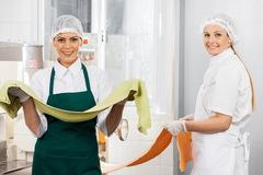 Happy Female Chefs Holding Pasta Sheets At Kitchen Stock Photography