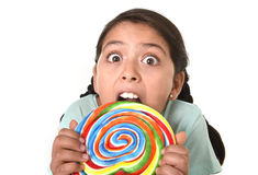 Happy female child holding big lollipop candy biting the candy with her teeth in freak crazy funny face expression Stock Image