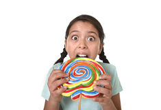 Happy female child holding big lollipop candy biting the candy with her teeth in freak crazy funny face expression Stock Photo