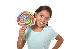 Happy female child holding big lollipop candy in cheerful face expression in kid love for sweet concept Stock Image