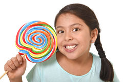 Happy female child holding big lollipop candy in cheerful face expression in kid love for sweet concept Stock Photos