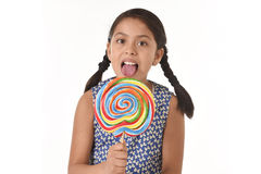 Happy female child holding big lollipop candy licking the candy with her tongue in sugar addiction Stock Photo