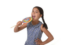 Happy female child holding big lollipop candy licking the candy with her tongue in sugar addiction Royalty Free Stock Images
