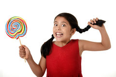 Happy female child holding big lollipop candy pulling pony tail with crazy funny face expression in sugar addiction Stock Photos