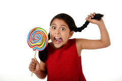 Happy female child holding big lollipop candy pulling pony tail with crazy funny face expression in sugar addiction Stock Photography