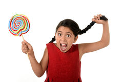 Happy female child holding big lollipop candy pulling pony tail with crazy funny face expression in sugar addiction Royalty Free Stock Photography