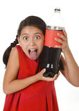 Happy female child holding big soda bottle against her face in crazy and over excited expression Stock Images