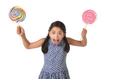 Happy female child holding two big lollipop in crazy funny face expression in sugar addiction Stock Images