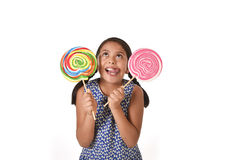 Happy female child holding two big lollipop in crazy funny face expression in sugar addiction Royalty Free Stock Images