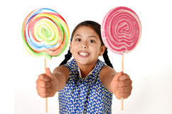 Happy female child holding two big lollipop in crazy funny face expression in sugar addiction Royalty Free Stock Photos