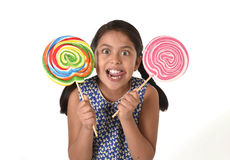 Happy female child holding two big lollipop in crazy funny face expression in sugar addiction Stock Photography