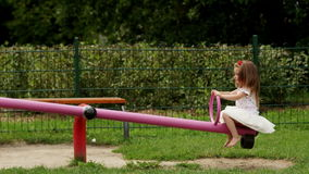 Happy Female Child in White Skirt and Shirt Playing on the Seesaw Outside During Summer Sunny Day. stock footage