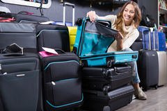 Happy female choosing  travel suitcase in store Royalty Free Stock Photos