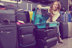 Happy female choosing  travel suitcase in store Royalty Free Stock Image