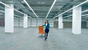 Happy female clerk dancing with a chair alone. 4K stock video footage