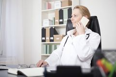 Happy Female Clinician Calling on Mobile Phone Royalty Free Stock Image