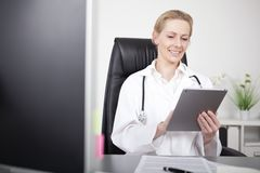Happy Female Clinician Using her Tablet Computer Stock Images