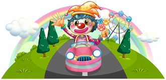 A happy female clown riding on a pink car Stock Photos