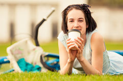 Happy female with coffee cup lying on grass Stock Images