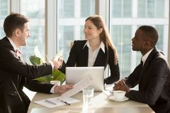 Businesswoman shaking hand to new business partner. Happy female company leader sitting at desk with her african american partner, shaking hand with satisfied Royalty Free Stock Images