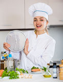 Happy female cook holding clock near prepared salmon Stock Photo
