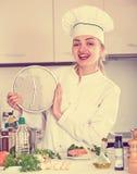 Happy female cook holding clock near prepared salmon Stock Image