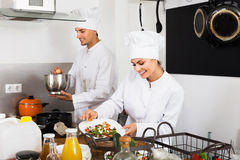 Happy female cook holding plate. Happy female cook wearing uniform holding plate with green salad Stock Photo