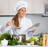 Happy female cook preparing veggies and smiling at home Royalty Free Stock Photo