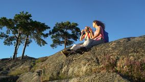 Happy Female Couple Drinking Champagne on a High Rock in the Sunshine. Nordic landscape with pine trees, cliffs and sea stock video footage